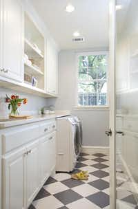 To maximize space in the narrow laundry room, Piaschyk turned to built-in cabinets and shelves aligned along one wall.(Photos by Sergio Garza - Sergio Garza Photography)