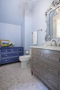 In renovating a powder room, designer Denise Piaschyk replaced the black wallpaper with a jewel-tone blue paint. The herringbone-pattern floor tiles( Sergio Garza  -  Sergio Garza Photography )