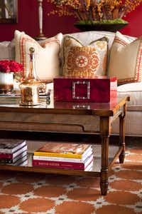 A cocktail table topped with a red lacquer box, glass decanter and mercury glass candle sits in front of a traditional sofa upholstered in a linen fabric.( Dan Piassick  -  Piassick Photography )