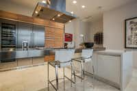 Purchased as unit from Cantoni, the contemporary kitchen has custom cabinetry, a stainless-steel island and sleek Gaggenau appliances.( Milton Johnson  -  Shoot2Sell Photography )