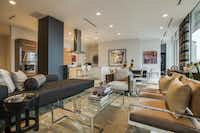 The living and dining areas of the penthouse residence are unified by contemporary upholstery in neutral tones accented with black.Milton Johnson  -  Shoot2Sell Photography