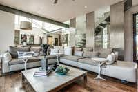 Exposed metal I-beams and a stainless-steel staircase with a Lucite hand rail complement the contemporary house. Built in 2010, it has four bedrooms and 4.5 baths.