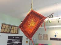 Variations of the God's eye, a yarn-weaving craft, are suspended from overhead fixtures.Melody Townsel