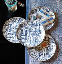 Blue and white porcelain plates recall ancient temple menorahs. $49.95/4. The complementary table runner is inspired by Miriam, sister and protector of the baby Moses, symbolized by a stylized hand. $69.95. At Williams-Sonoma, NorthPark Center and Highland Park Village in Dallas; Preston Park Village in Plano; and williams-sonoma.com.