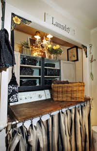 A vintage-style sign marks the laundry area. The machines are skirted and covered with a removable folding board to use as a work surface.
