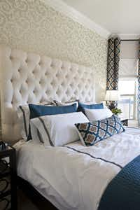 Simple linens with a dark trim set off the wallpaper and curtains in the master bedroom.