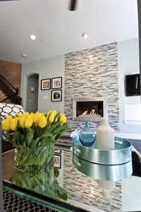 A fireplace enhanced with frosted glass tiles gives the living room  a custom feel.