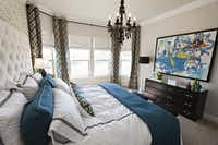 The master bedroom serves up more pattern -- in the wallpaper, curtains and a pillow on the bed. The towering headboard was a Craigslist find.