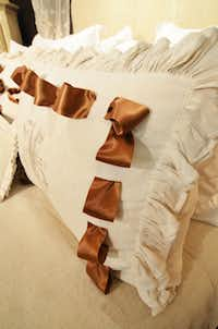 De Balthazar weaves in a simple silk ribbon to change the look of this antique linen pillow sham with a ruffled edge.