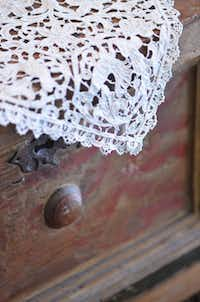 Antique lace can dress up a formal dresser or table as well as primitive and contemporary pieces.
