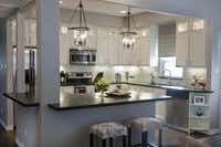 """The new kitchen totally transformed the house,"" Emily Hewett says. It went high-style with granite countertops, a marble backsplash and cabinets with illuminated glass fronts at the top along the ceiling."