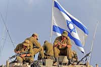 Israeli soldiers sat on their armored personnel carrier as they cleaned their weapons at a staging area on the Israel-Gaza border Sunday. Israel warned Palestinians through fliers and phone calls that major attacks are to come.( Lefteris Pitarakis  -  The Associated Press  )
