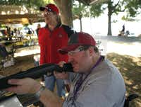 Tim Stone of Dallas took aim with an air rifle as Turning Point volunteer Rhonda Esakov watched.