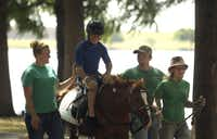 Jason Lauchner, 13, of Grand Prairie enjoyed a horseback ride with help from his sister Kaitlynn (right) and volunteers  Maddison Garrett and Josh Smith.