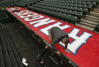 Lance Tucker and Dusty Keene put finishing touches on the Rangers' dugout Thursday. The team has spent about $35 million on stadium upgrades the past three years.