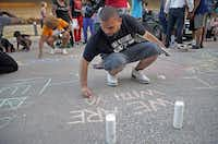 """Ramon Mejia joined other participants in a vigil Monday evening for Christian Taylor by using chalk to write messages such as """"We are with you"""" on the pavement outside the Arlington Police Department. About 60 people with Dallas-based Mothers Against Police Brutality attended the vigil.( G.J. McCarthy  -  Staff Photographer )"""