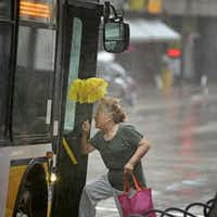 A woman struggled against rain and wind as she boarded a bus along Elm Street in downtown Dallas on Wednesday. The remnants of Tropical Storm Bill arrived in the Dallas area Wednesday morning, bringing a deluge to some parts but little flooding.( G.J. McCarthy  -  Staff Photographer )