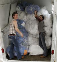 Emily Benton (left) and Kelsi Mew loaded bags filled with linens into a horse trailer headed for Moore, Okla., on Friday.