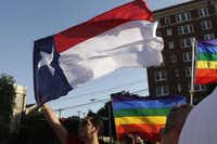 Frank Garza flies a Texas flag as the Dallas lesbians and gays and allies gathered for the Day of Decision rally at the Legacy of Love Monument in Dallas on Wednesday.