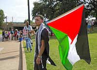 Mahir Hassan of Arlington  brought the Palestinian flag to a rally at Dealey Plaza in on Sunday.(Brittany Sowacke - Staff Photographer)