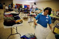 Ana Hallaman helps fold clothing at Sacred Heart Catholic Church Wednesday, July 2, 2014 in McAllen, Texas.G.J. McCarthy  -  Staff Photographer
