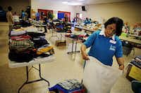 Ana Hallaman helps fold clothing at Sacred Heart Catholic Church Wednesday, July 2, 2014 in McAllen, Texas.G.J. McCarthy  -  Staff Photographer