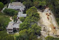 Heavy equipment is carving out an underground garage at the Highland Park home of Harlan Crow. Neighbors wonder if it's part of a plan to open his home museum to more people. Crow says it will give his kids a place to play on a rainy day.(G.J. McCarthy - Staff Photographer)