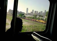The downtown Dallas skyline is seen through the window of a northbound DART Blue Line train.(G.J. McCarthy - Staff Photographer)