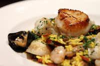 Paella Risotto is accompanied by duck confit, merguez lamb sausage, rock shrimp, halibut and cured tomatoes.