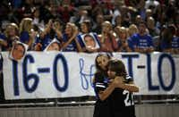 Coppell High School students Courtney Echerd and Tiffany Breitenwischer embraced following a moment of silence before the Cowboys' game against Flower Mound.