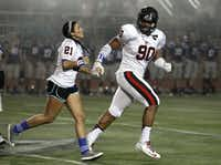 Coppell student Jordan Logan, sister of Jacob Logan, ran off the field with  Solomon Thomas after participating in the coin toss before the Cowboys played Flower Mound.
