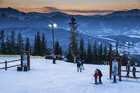 Skiers and snowboarders gather at the the Schoolmarm trail at dusk on Dercum Mountain.