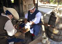 Costumed interpreters at Colonial Quarter repair weapons.