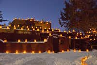 Plaza Fatima on Christmas Eve __ Caption: Thousands of candlelit farolitos top adobe walls along Canyon Road in Santa Fe. Hundreds of locals enjoy the sight while walking the road on Christmas Eve.