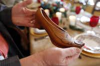 Michael Hamilton, a decorator, stylist, floral designer and co-owner of the shop La Foofaraw, holds what he believes is a French-style clog.