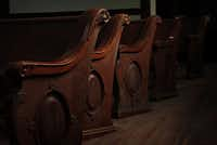 Original, late 19th century pews are illuminated by nearby windows.