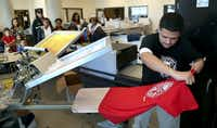 Graphic Arts student Juan Villarreal makes a screen print T-shirt being given away at Dubiski Career High School.