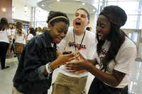 Allen High School students Michelle Hester (left) and Jessica Okpala shared a smartphone laugh with Linden High School student Anthony Wohlrav of New Jersey at a breakfast on Friday.
