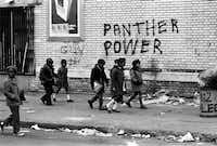Children walk past Black Panthers graffiti in a scene from The Black Panthers: Vanguard of the Revolution.(Stephen Shames)