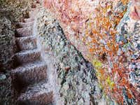 Multi-colored lichens appear on rock by steps carved up a slope by the Civilian Conservation Corps in the 1930s.