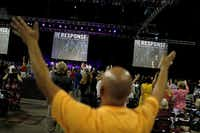 People raise their hands in prayer as they listen to Radiant Worship perform before Gov. Rick Perry's prayer event Saturday at Reliant Stadium in Houston.
