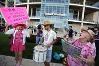 """From left: Shelley Buschur, Kirk Suddreath and a woman who went by the name Courtney Code Pink sings songs in protest outside """"The Response"""" event Saturday at Reliant Stadium in Houston."""