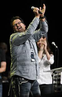 """Johhny Fernandez of Encourager Church sings during """"The Response"""" event Saturday at Reliant Stadium in Houston."""