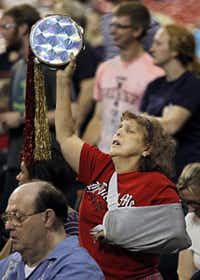"""Delores Cox of Houston raises a tambourine during prayer at the """"The Response""""  event Saturday at Reliant Stadium in Houston."""