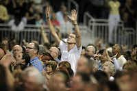 """Justin Neuhaus of San Marcos raises his hands in worship during  """"The Response"""" on Saturday in Houston."""