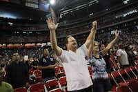 """Dan Seal (center) and his wife, Elizabeth, raise their hands in worship during """"The Response"""" on Saturday in Houston."""