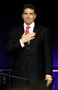 """Gov. Rick Perry holds his hand to his heart as he prepares to give final remarks during """"The Response"""" on Saturday."""