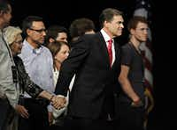 """Gov. Rick Perry holds hands with participants on stage after giving final remarks during """"The Response"""" on Saturday."""
