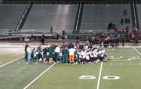 Players from the Waxahachie and Ennis JV teams gathered in prayer after Triston Simpler was taken by ambulance to the hospital last Thursday night in Waxahachie.