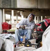 """Wyken Masters, 29, looks up while sitting near his tent at """"Tent City."""" (Andy Jacobsohn/The Dallas Morning News)"""
